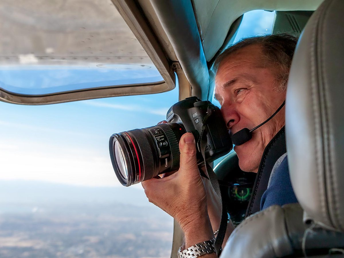 Press photo of Mark Holtzman taking aerial photographs through the window of his Cessna airplane